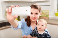 Mother and baby photographing selfie themselves by mobile